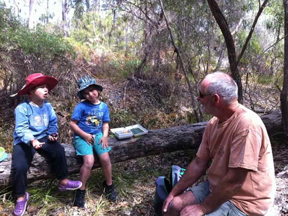 Photo of Spirit of Play students listening to their teacher while sitting on a log