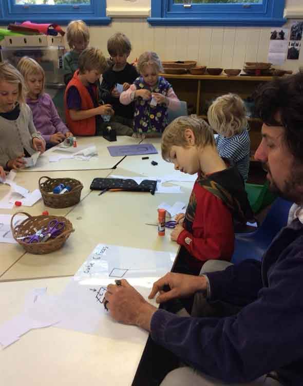 Photo of Spirit of Play teacher helping students in an arts and craft class