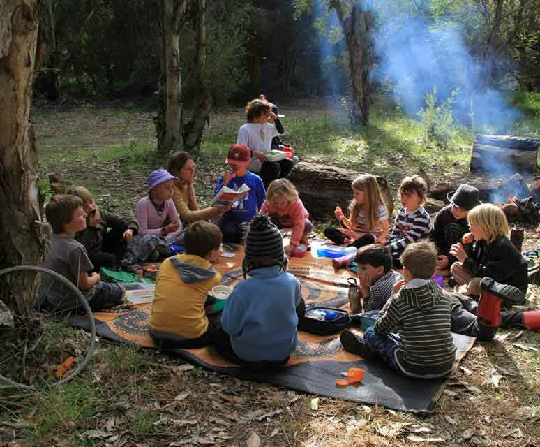 Photo of Spirit of Play students eating lunch next to a campfire during a cultural excursion