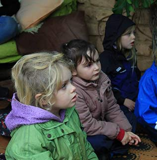 Photo of a group of Spirit of Play students listening to their teacher during class