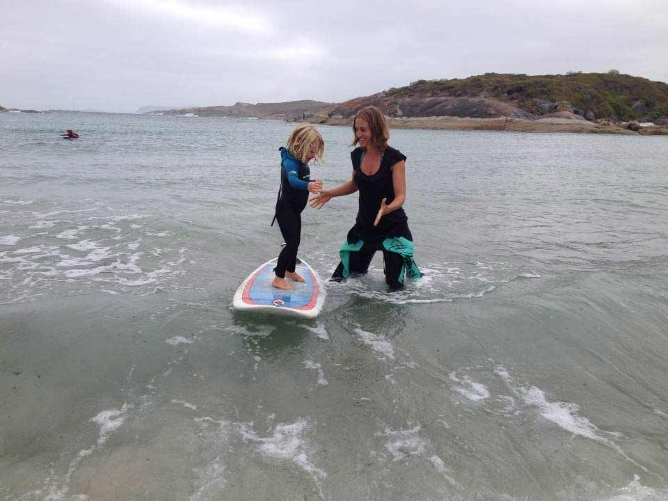 Spirit of Play teacher helping teach Violet how to stand on a surfboard on an excursion