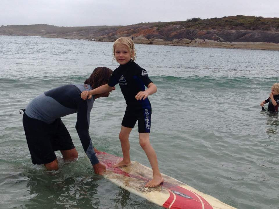 Photo of Spirit of Play student, Fin, enjoying a surfing lesson
